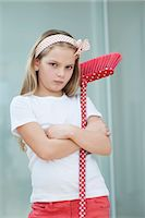 Portrait of an angry girl with broom Stock Photo - Premium Royalty-Freenull, Code: 693-06379429