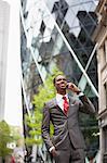 Happy African American businessman using cell phone outside building Stock Photo - Premium Royalty-Free, Artist: Uwe Umsttter, Code: 693-06379471