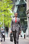 Happy African American businessman with bag walking on street Stock Photo - Premium Royalty-Free, Artist: Eyecandy Pro, Code: 693-06379473
