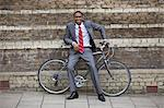 Portrait of a happy young businessman with bicycle against brick wall Stock Photo - Premium Royalty-Free, Artist: Siephoto, Code: 693-06379474