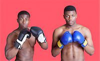 Portrait of two African American boxers wearing gloves over red background Stock Photo - Premium Royalty-Freenull, Code: 693-06379528