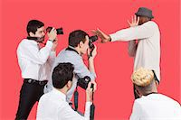 Young male celebrity shielding face from photographers over red background Stock Photo - Premium Royalty-Freenull, Code: 693-06379566