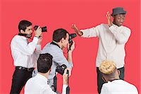 Young male celebrity shielding face from photographers over red background Stock Photo - Premium Royalty-Freenull, Code: 693-06379567