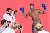 Paparazzi taking photographs of male boxer over red background Stock Photo - Premium Royalty-Freenull, Code: 693-06379569