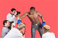 Paparazzi taking photographs of male boxer over red background Stock Photo - Premium Royalty-Freenull, Code: 693-06379570