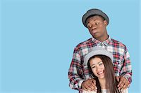 Bored African American man with smiling girlfriend over blue background Stock Photo - Premium Royalty-Freenull, Code: 693-06379587