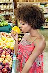 Side view of African American woman smelling fresh orange at supermarket Stock Photo - Premium Royalty-Free, Artist: AWL Images, Code: 693-06379618