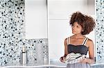 Young African American woman looking at designed wall as she holds design swatches Stock Photo - Premium Royalty-Free, Artist: Cultura RM, Code: 693-06379626