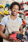 Portrait of an African American male store clerk holding electronic tool Stock Photo - Premium Royalty-Free, Artist: Blend Images, Code: 693-06379632