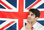 Thoughtful young man with hand on chin against British flag Stock Photo - Premium Royalty-Free, Artist: Cultura RM, Code: 693-06379642