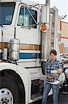 Woman looking at clipboard while standing by flatbed truck Stock Photo - Premium Royalty-Free, Artist: Michael Mahovlich, Code: 693-06379647