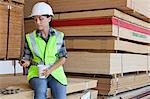 Female industrial worker taking break from work at timber yard Stock Photo - Premium Royalty-Free, Artist: Blend Images, Code: 693-06379680