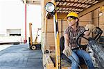 Female industrial worker looking away while driving forklift truck Stock Photo - Premium Royalty-Free, Artist: Blend Images, Code: 693-06379687