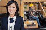 Portrait of woman smiling while female industrial worker driving forklift truck in background Stock Photo - Premium Royalty-Free, Artist: Blend Images, Code: 693-06379690