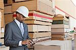 African American male contractor using tablet PC with stacked wooden planks in background Stock Photo - Premium Royalty-Free, Artist: Blend Images, Code: 693-06379701