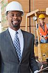 Portrait of African American male engineer smiling with female worker in background Stock Photo - Premium Royalty-Free, Artist: Uwe Umstätter, Code: 693-06379702