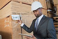 African American male contractor using tablet PC while inspecting wooden planks Stock Photo - Premium Royalty-Freenull, Code: 693-06379710