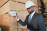 African American male contractor using tablet PC while inspecting wooden planks Stock Photo - Premium Royalty-Free, Artist: Uwe Umstätter, Code: 693-06379710
