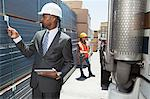 African American male engineer inspecting planks while female worker standing by flatbed truck Stock Photo - Premium Royalty-Free, Artist: Uwe Umstätter, Code: 693-06379717
