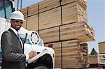 Portrait of African American male contractor writing notes while standing by logging truck Stock Photo - Premium Royalty-Free, Artist: Blend Images, Code: 693-06379722