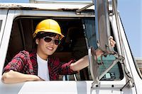 female truck driver - Female industrial worker adjusting mirror while sitting in logging truck Stock Photo - Premium Royalty-Freenull, Code: 693-06379729
