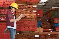 Side view of an Asian female industrial worker working on tablet PC with stacked wooden planks in background Stock Photo - Premium Royalty-Freenull, Code: 693-06379734