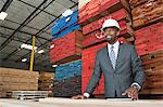 An African American male contractor standing in front of stacked wooden planks Stock Photo - Premium Royalty-Free, Artist: Uwe Umstätter, Code: 693-06379741