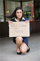 Young Indian businesswoman holding 'Will Work for Food' sign Stock Photo - Premium Royalty-Freenull, Code: 693-06379902