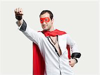 Young man wearing superhero costume against gray background Stock Photo - Premium Royalty-Freenull, Code: 693-06379908