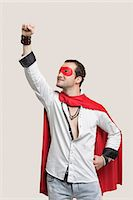 Young man in superhero costume standing against gray background Stock Photo - Premium Royalty-Freenull, Code: 693-06380036