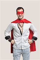 superhero costume - Portrait of young man in superhero costume with hands on hip standing against gray background Stock Photo - Premium Royalty-Freenull, Code: 693-06380042