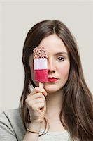 Portrait of young woman with red lips holding ice cream bar against gray background Stock Photo - Premium Royalty-Freenull, Code: 693-06380045