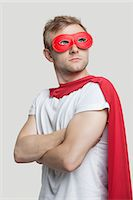 superhero costume - Young man in red superhero costume looking up over gray background Stock Photo - Premium Royalty-Freenull, Code: 693-06380065
