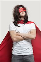 Young man in super hero costume standing with arms crossed against gray background Stock Photo - Premium Royalty-Freenull, Code: 693-06380066