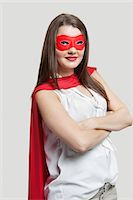 Portrait of a young woman in super hero costume over gray background Stock Photo - Premium Royalty-Freenull, Code: 693-06380079