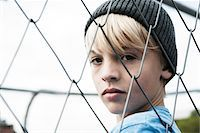 superior - Portrait of Boy Looking Through Chain Link Fence, Mannheim, Baden-Wurttemberg, Germany Stock Photo - Premium Royalty-Freenull, Code: 600-06382847