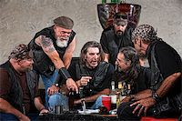 Biker gang members talking and drinking with weapons Stock Photo - Royalty-Freenull, Code: 400-06396529