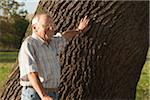 Man Standing by Tree, Lampertheim, Hesse, Germany Stock Photo - Premium Royalty-Free, Artist: Uwe Umsttter, Code: 600-06397413