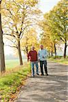 Senior Men Walking on Tree-lined Path in Autumn, Lampertheim, Hesse, Germany Stock Photo - Premium Royalty-Free, Artist: Uwe Umsttter, Code: 600-06397472