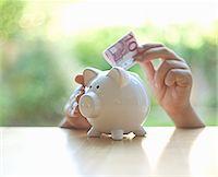 savings - Hang putting Euro note in piggy bank Stock Photo - Premium Royalty-Freenull, Code: 649-06400383