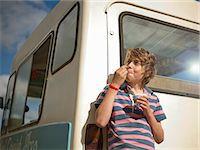 Boy eating ice cream by truck Stock Photo - Premium Royalty-Freenull, Code: 649-06400392