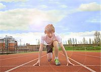 race track (people) - Boy crouched at starting line on track Stock Photo - Premium Royalty-Freenull, Code: 649-06400417