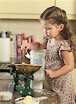Girl weighing ingredients in kitchen Stock Photo - Premium Royalty-Free, Artist: Photocuisine, Code: 649-06400423