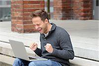 streaming - Man using laptop and cheering Stock Photo - Premium Royalty-Freenull, Code: 649-06400691