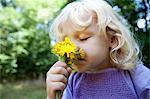 Girl smelling wildflowers outdoors Stock Photo - Premium Royalty-Free, Artist: Ikonica, Code: 649-06400729