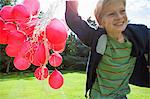 Boy carrying bunch of balloons outdoors Stock Photo - Premium Royalty-Free, Artist: Ikon Images, Code: 649-06400835