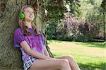 Girl listening to headphones in park Stock Photo - Premium Royalty-Free, Artist: Blend Images, Code: 649-06400855