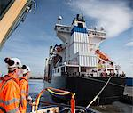 Workers on tug boat overlooking ship Stock Photo - Premium Royalty-Free, Artist: ableimages, Code: 649-06400931