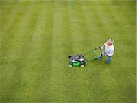 Man wearing headphones and mowing lawn Stock Photo - Premium Royalty-Freenull, Code: 649-06400994