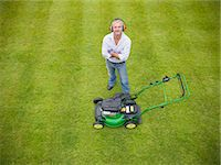 Man standing with lawn mower Stock Photo - Premium Royalty-Freenull, Code: 649-06400995
